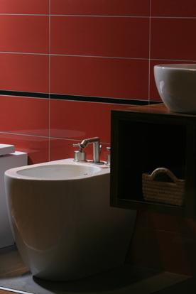 Sytě červený lesklý obklad, masivní stolek pod umyvadlo z exotického dřeva ovangkol, baterie Gessi Ovale, keramika Catalano systema C.